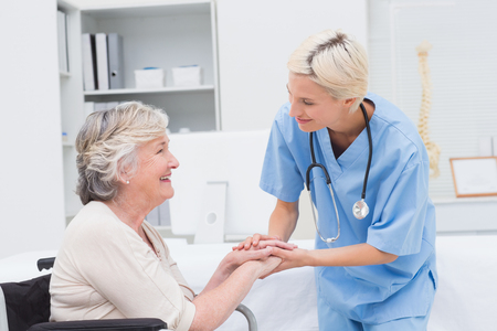 holding hand: Friendly nurse holding senior patients hands in clinic Stock Photo