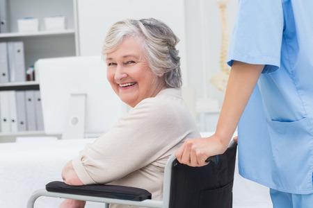 Retrato do paciente sênior na cadeira de rodas que está sendo empurrada pela enfermeira na clínica
