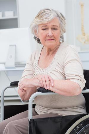 chory: Przemyślany smutny starszy pacjent siedzi na wózku inwalidzkim w klinice