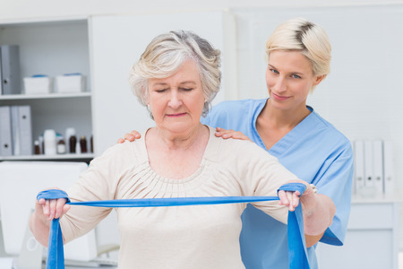 occupation: Portrait of confident nurse assisting senior woman in exercising with resistance band in clinic