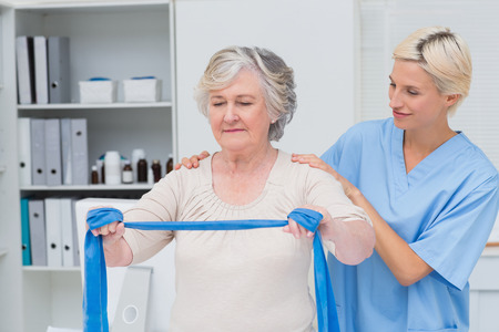 resistance: Nurse helping senior patient in exercising with resistance band in clinic