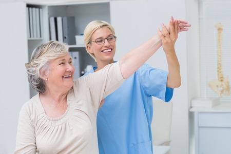 fisico: Enfermera de sexo femenino feliz que ayuda al paciente mayor en el ejercicio a la cl�nica