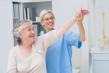 Happy female nurse helping senior patient in exercising at clinic