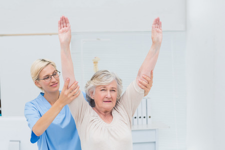 physical test: Female nurse helping female patient in exercising at clinic Stock Photo