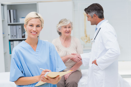 Portrait of nurse making reports while doctor and patient shaking hands in background at clinic photo