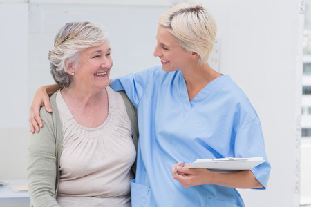Happy friendly nurse with arm around senior patient standing in clinic Stockfoto