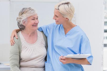 nurse clipboard: Happy friendly nurse with arm around senior patient standing in clinic Stock Photo