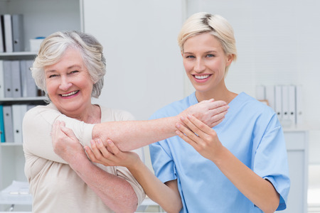 woman with camera: Portrait of smiling female nurse assisting senior patient in raising arm at clinic Stock Photo