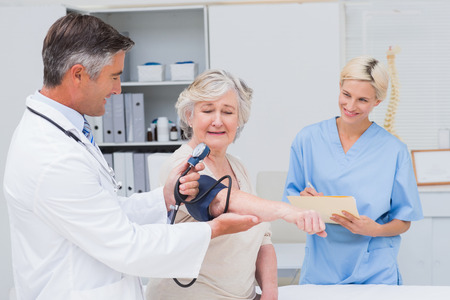 noting: Male doctor checking senior patients blood pressure while nurse noting it in clinic