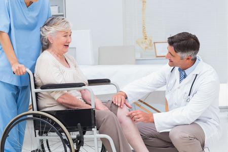 de rodillas: Hombres m�dico ortop�dico examinar la rodilla mujer mayor en una cl�nica