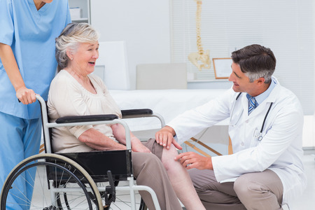 Male orthopedic doctor examining senior womans knee in clinic