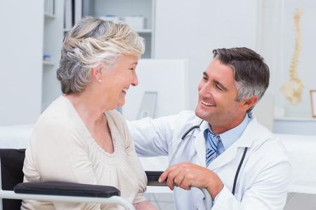 paciente: Doctor de sexo masculino feliz que mira la paciente en la cl�nica Foto de archivo