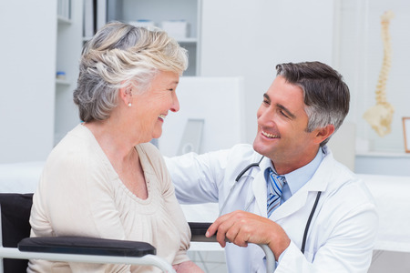 Doctor de sexo masculino feliz que mira la paciente en la clínica