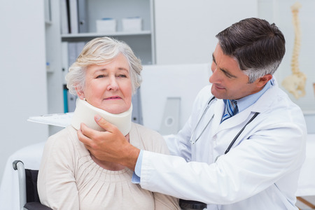 neck brace: Male doctor examining senior patient wearing neck brace in clinic