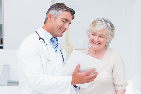 doctor examining woman: Happy doctor and patient discussing over reports in clinic