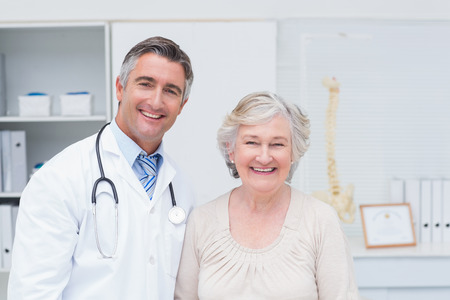 Portrait of happy male doctor and female patient in clinic