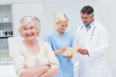 medical test: Portrait of senior female patient smiling while doctor and nurse discussing in background at clinic