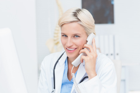 conversing: Portrait of confident female doctor using land line phone in clinic