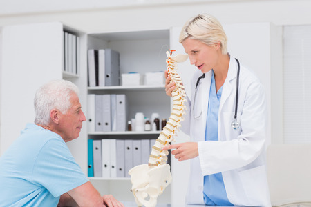 Female doctor explaining anatomical spine to senior man in clinic