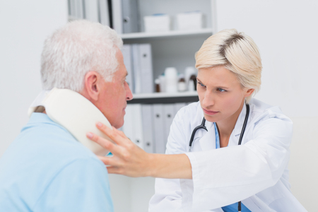 medical exam: Female doctor examining senior patient wearing neck brace in clinic