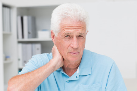 senior man on a neck pain: Portrait of senior male patient suffering from neck ache in clinic Stock Photo