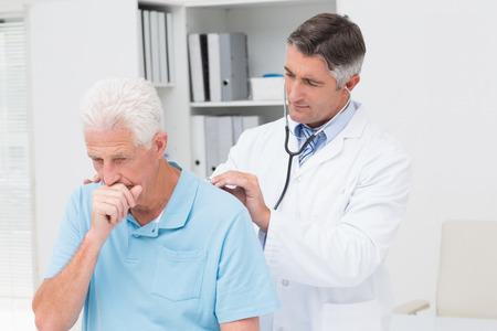 tosiendo: Hombre m�dico examinando a toser al paciente mayor en la cl�nica Foto de archivo