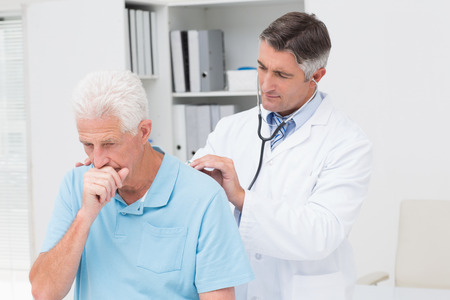 examining: Male doctor examining coughing senior patient in clinic