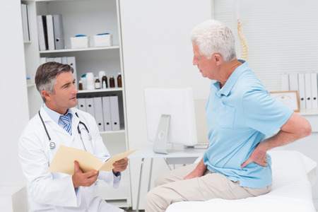 pain: Male doctor discussing reports with senior patient suffering from backache in clinic