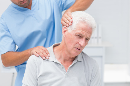 physical test: Physiotherapist giving physical therapy to senior male patient in clinic Stock Photo
