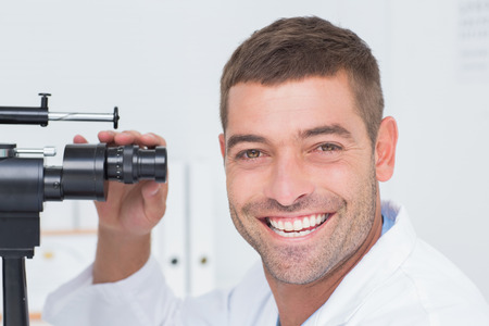 slit: Portrait of happy optician using slit lamp in clinic