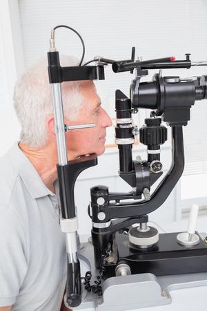 slit: Paciente de sexo masculino mayor que mira en la l�mpara de hendidura en la cl�nica