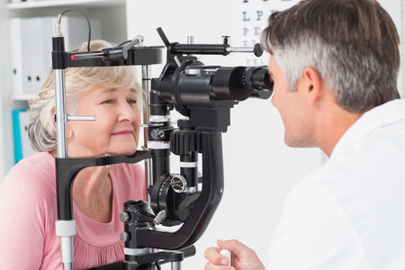 Zijaanzicht van opticien onderzoekt senior vrouwelijke patiënt door middel van spleetlamp in kliniek