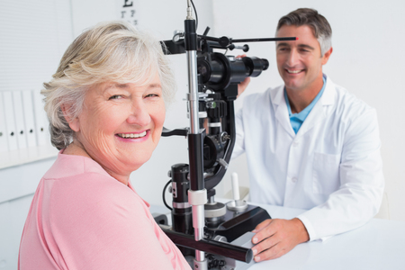 Portrait of senior woman smiling while sitting with optician in clinic