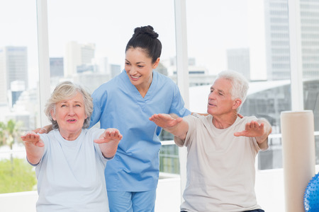 Happy trainer assisting senior couple to exercise in gym