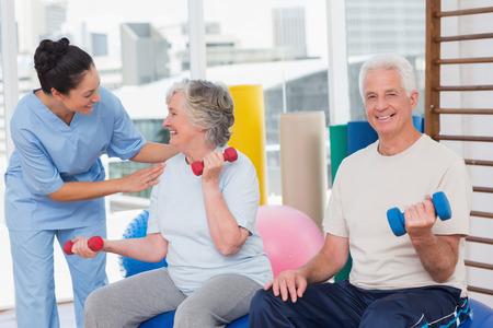 Gelukkig trainer communiceren met senior vrouw zat bij mens in gymnastiek