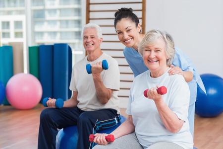 física: Retrato de mujer instructor feliz con pareja de ancianos en el gimnasio