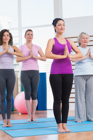 clasped: Full length of female friends with hands clasped exercising in gym