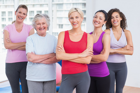 clases: Retrato de los amigos de sexo femenino confidente de pie brazos cruzados en el gimnasio