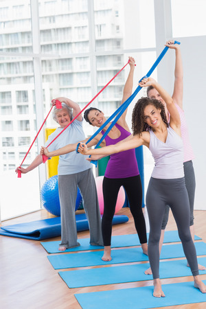 Full length portrait of happy female friends exercising with resistance bands in gym 版權商用圖片