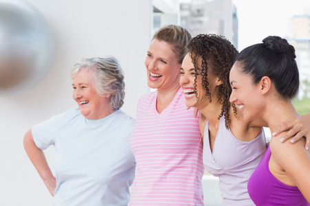 arms around: Happy female friends standing arms around in fitness studio Stock Photo