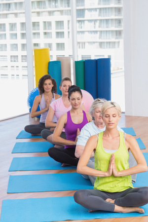 Row of fit women meditating in fitness class photo