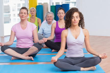 Fit women practicing lotus position in gym class Stock Photo