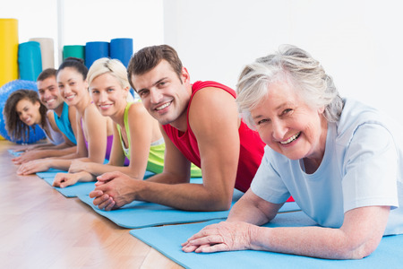 Portrait of happy senior woman with friends lying on exercise mats at gym photo