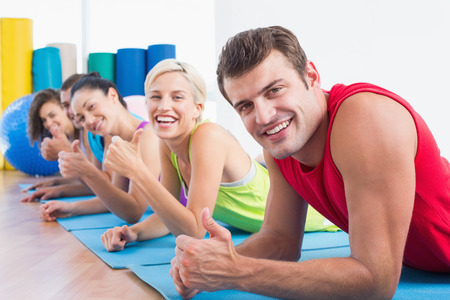 Portrait of happy man with friends gesturing thumbs up while lying on exercise mats at gym photo