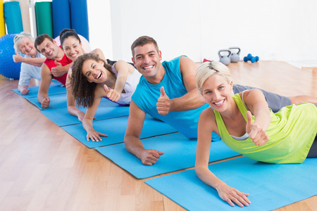 Portrait of happy people on exercise mats gesturing thumbs up at gym photo
