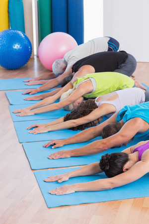 Row of people practicing child pose on exercise mats in gym photo