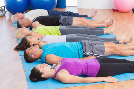 Fit men and women meditating on exercise mats in fitness club photo