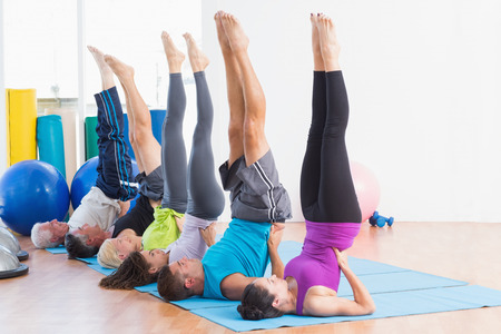 women working out: Full length of men and women working out in an fitness class