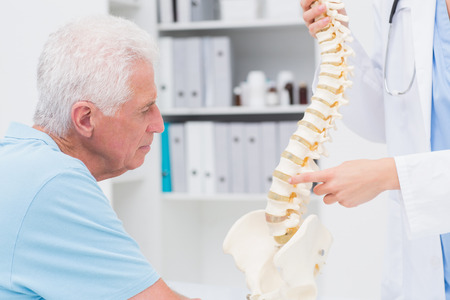 orthopedic: Cropped image of female doctor explaining anatomical spine to senior man in clinic Stock Photo