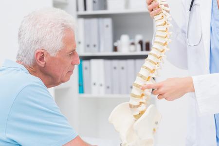 Recorta la imagen de mujer médico explicando columna vertebral anatómica al hombre mayor en la clínica